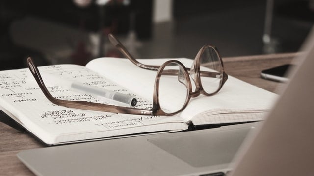 research notepad on table with glasses